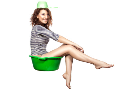 Funny girl sitting in a green wash rides on a white background  photo