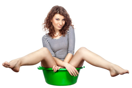 Funny girl sitting in a green wash rides on a white background