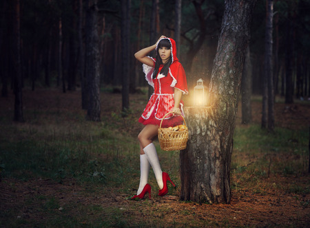 Beautiful girl in a red raincoat alone in the woods with a basket in which cakes  photo