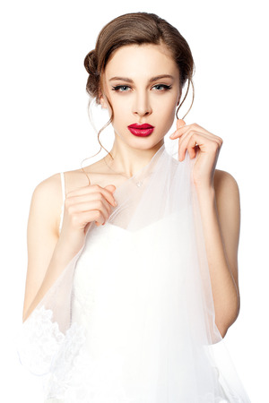 Portrait of a beautiful bride with red lips, she is holding a veil in her hands  photo