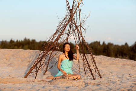 Beautiful girl in a tent shaman on the sand