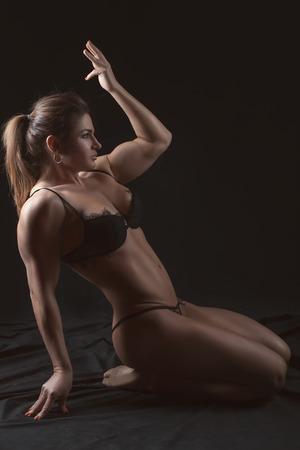 Girl bodybuilders shows his muscles on black background  photo