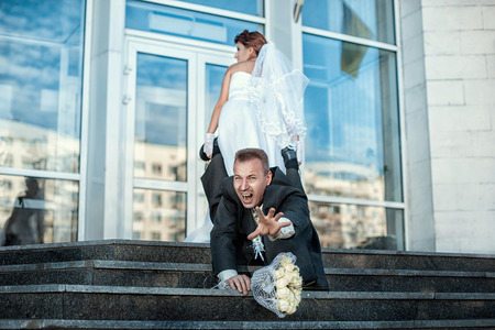 Bride groom grabbed his leg and pulls the wedding