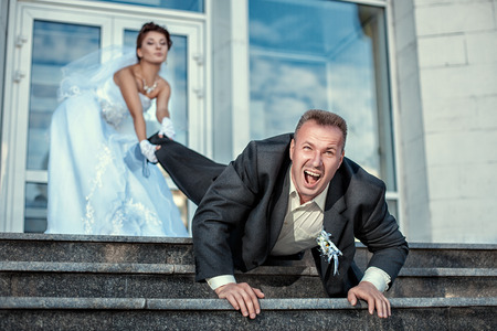 escape: Bride leg pulls groom at the wedding  Stock Photo