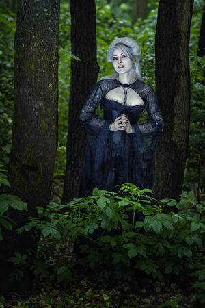 Beautiful girl witch in black dress stands alone in the woods  Stock Photo - 28578087