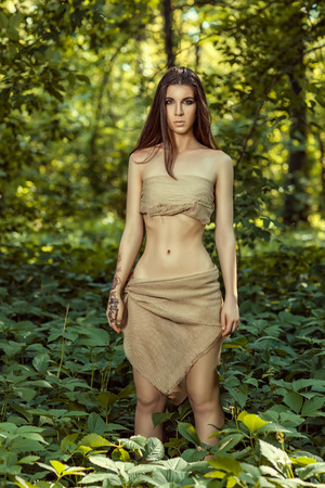 loincloth: Savage woman with long hair standing in the woods