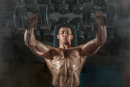 Bodybuilder man lying exercisers squeezing large dumbbells