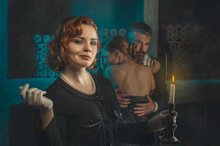 beguin: Redhead retro girl with a candle in gloves  Stock Photo