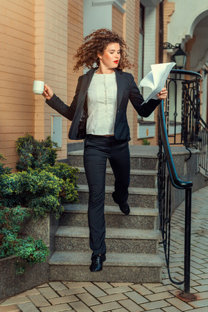 promptly: Woman runs mug in one hand and in the other documents