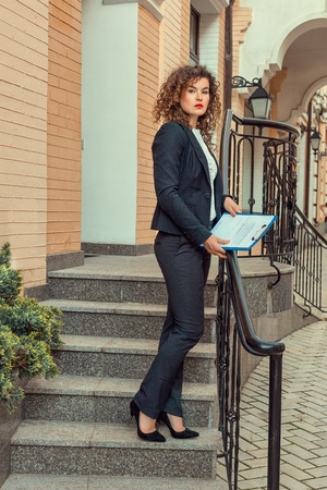 stringent: Woman with documents standing outside his office  Stock Photo