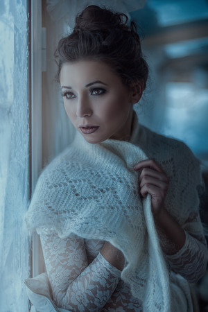 Portrait of beautiful girl near the window, her shawl