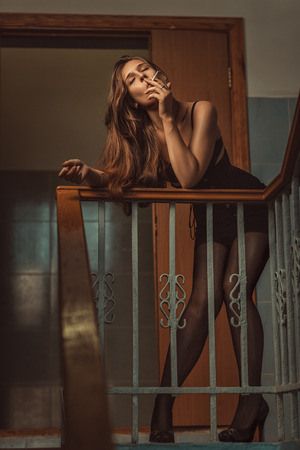 Woman of easy virtue smoke on the steps  Stock Photo