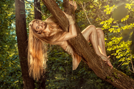 tarzan: Wild guy with long hair weighs on the tree in the forest