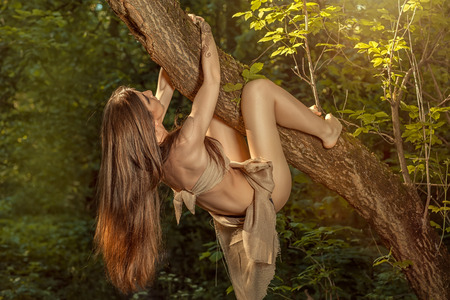barbarian: Wild girl climbs a tree in the forest  Stock Photo