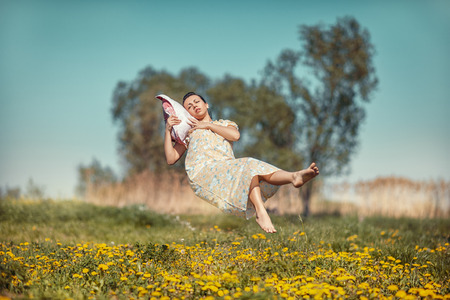 weightlessness: Girl lying on a cushion hovers over the field in weightlessness  Stock Photo