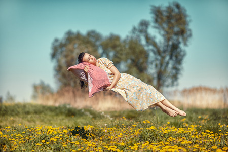 Girl hovers and sleeps on a pillow over a beautiful meadow