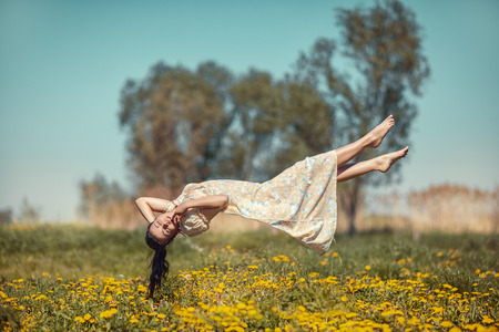 Girl floating in weightlessness over the meadow of dandelions
