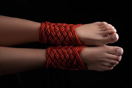 sadism: Shibari pattern on two legs female closeup. Stock Photo