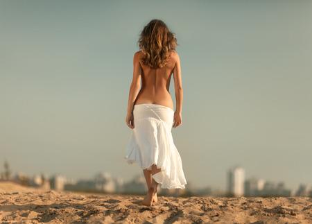 nue plage: Fille avec un dos nu est vers la ville.