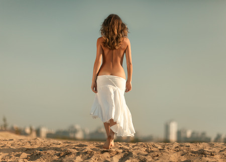 nude outdoors: Girl with a bare back is towards the city.