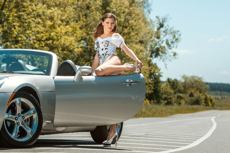 Beautiful girl opened the door of a sports car on the road. Stock Photo
