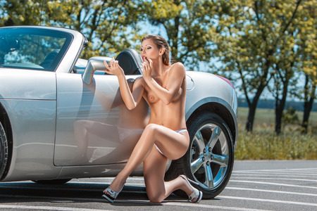 Erotic beautiful girl standing near the car and looking in the mirror, she was naked.