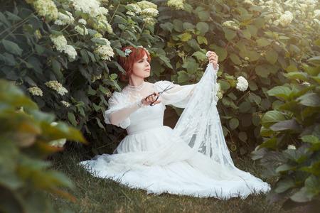 confect: Tra la ragazza arbusti da fiore con le forbici rende un abito da sposa.