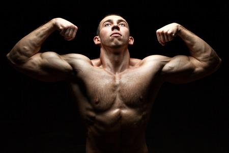 Portrait of a Bodybuilder, Muskeln aufzubauen und zeigt uns gleichzeitig nach oben auf schwarzem Hintergrund. Standard-Bild - 32631080