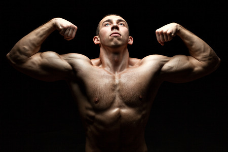 punch press: Portrait of a bodybuilder who build muscle and shows us at the same time looking up on black background. Stock Photo