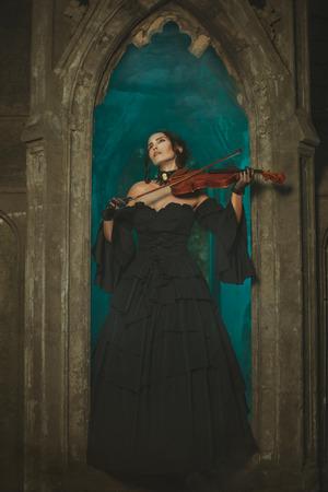 opening window: Magical Girl medieval tocando el viol�n en la noche en la ventana de apertura del castillo.