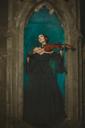 Magical medieval girl playing the violin at night in the opening window of the castle. photo