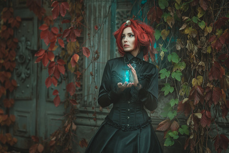 Fabulous girl with red hair, she is holding an hourglass. At the door of the castle.