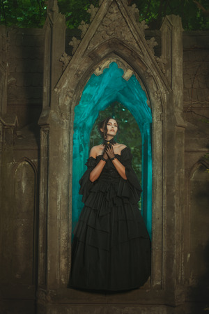 Girl in the window of the castle stands the night in the Gothic manner. photo