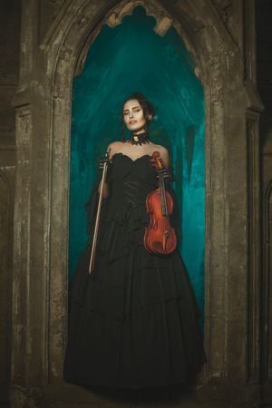 In the window there is a girl witch and smiling. In the hands of her violin. photo