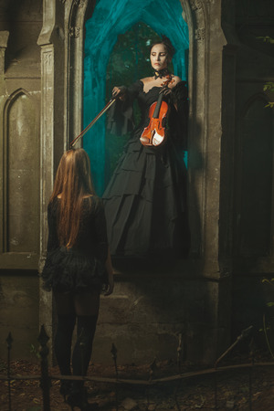 witchery: Night in the castle ghost is a girl with a violin in his hands and shows a bow on the girl ghost. Stock Photo