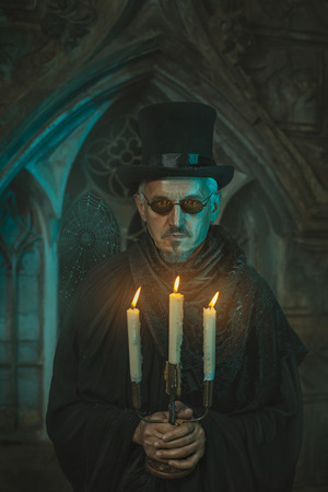 witchery: Strange and scary man standing with a candelabrum in which candles are burning. Men behind the old castle.