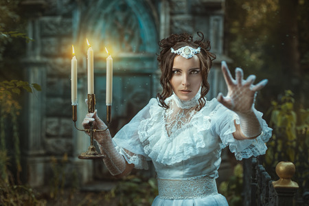 duskiness: The evening darkens. Girl with a candelabra in hand in which candles are burning. Girl scares us and shouts inducing intense fear. Stock Photo