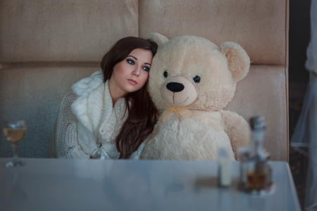 rueful: Sad girl with toy bear sitting at the table.