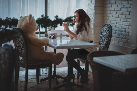 Girl sitting in a restaurant with a bear face to face and sad.