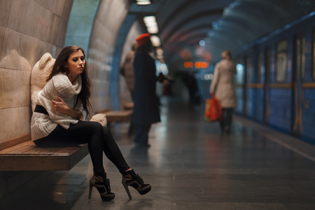 wretched: Sad girl sitting on a bench in the subway. Stock Photo
