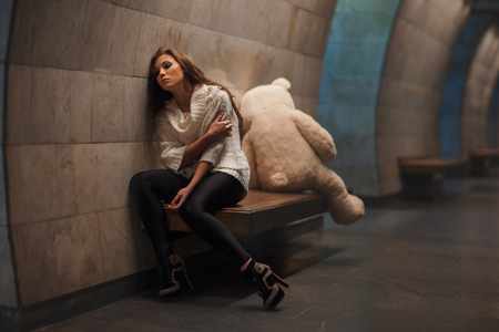 rueful: Girl sitting on a bench facing away from the toy bear, they quarreled and sadness.