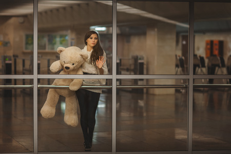 Girl with teddy bear in his hands waving goodbye hand, it is very sad. Stock Photo