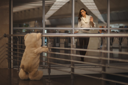 rueful: Sad girl waving, she says goodbye with a teddy bear and it Stock Photo