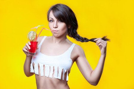 colleen: Girl drinking cocktail on her short tank top, on a yellow background.
