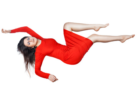 Levitates woman in a red dress, she spread her arms and legs, on white background. Stock Photo