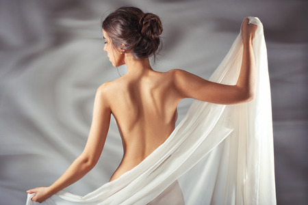 nude pose: Woman with bare back is worth having covered with a cloth that is transparent.
