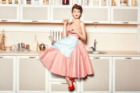 Woman in an apron in the kitchen drinking from a cup sitting on the table. Фото со стока