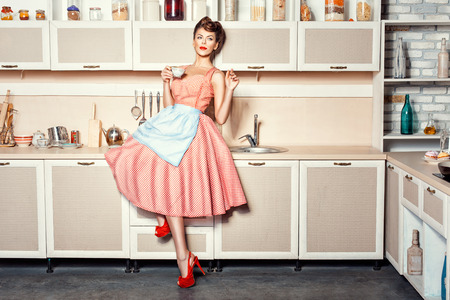 retro housewife: Woman in an apron in the kitchen drinking from a cup and waving. Stock Photo
