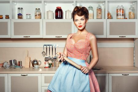 Een vrouw in schort met deegrol ter beschikking in de keuken.