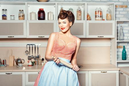 Das Mädchen in den Händen von einem Nudelholz, ist es in der Küche. Standard-Bild - 34459544